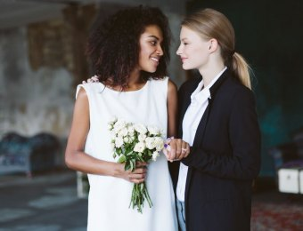 Young woman with blond hair in black suit and smiling african american woman with dark curly hair in white dress with bouquet of flowers in hand happily looking at each other on wedding