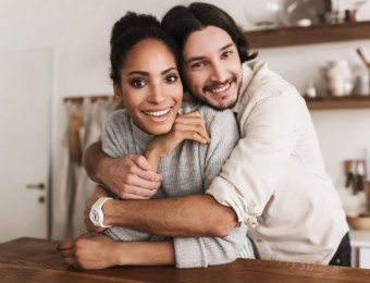 Smiling man dreamily embracing beautiful african american woman joyfully looking in camera together. Young international couple happily spending time in kitchen at home